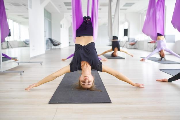 Aerial anti-gravity yoga, groepstraining met hangmatten. een mix van fitness, pilates en dansoefeningen. vrouwen op yogi-training in sportstudio