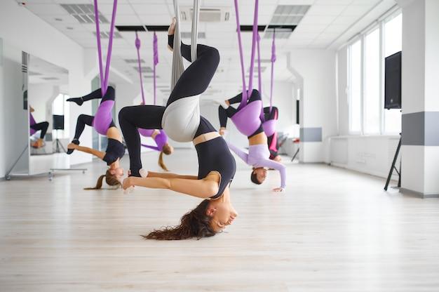 Aerial anti-gravity yoga, vrouwelijke groepstraining, hangmatten. een mix van fitness, pilates en dansoefeningen. vrouwen op yogi-training in sportstudio