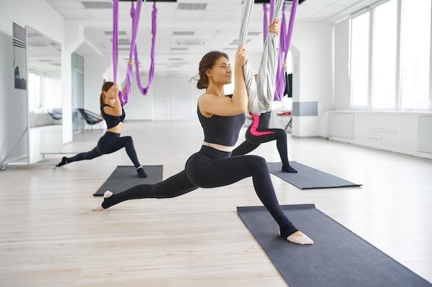 Aerial of anti-zwaartekracht yoga, groepstraining, hangmatten. een mix van fitness, pilates en dansoefeningen. vrouwen op yogi-training in de sportschool, fit levensstijl