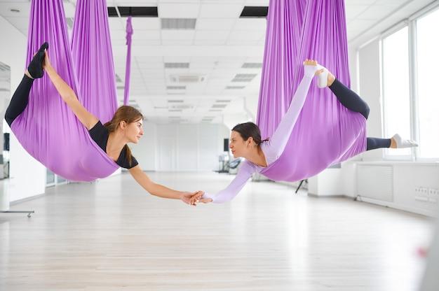 Aerial of fly yogastudio, vrouwelijke groepstraining, hangmatten hangen. een mix van fitness, pilates en dansoefeningen. vrouwen op yogi-training in de sportschool