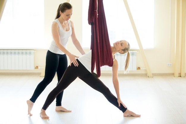 Aerial yoga instructeur helpen vrouw om uitgebreide driehoek te maken