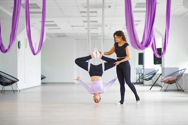 Aerial yoga, vrouw en vrouwelijke instructeur, training met hangmatten. een mix van fitness, pilates en dansoefeningen. vrouwen op yogi-training in sportstudio