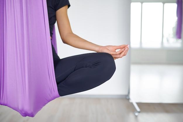 Aerial yoga, vrouw op hangmat, meditatie. een mix van fitness, pilates en dansoefeningen. vrouwelijke persoon op yogi training in sportstudio