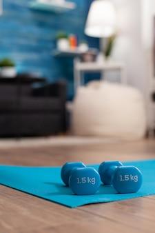 Aërobe lege woonkamer met niemand erin met fitness-halters die op yogamat staan, wachtend op sporter die bij wellness-training werkt en fysieke oefeningen doet