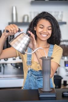 Aeropress, koffie. jonge donkerharige vrouw met opgeheven ketel in handen die zich achter toonbank dichtbij luchthaven in coffeeshop bevinden