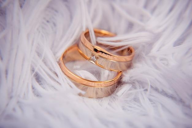 Afbeelding bevat een gouden diamanten ring liggend op witte veren. trouwringen, huwelijk, verloving, luxe, sieraden, etc.