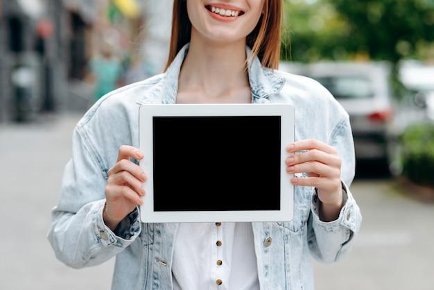 Afbeelding bijsnijden een meisje met zwart mockup-scherm van ipad in haar handen.