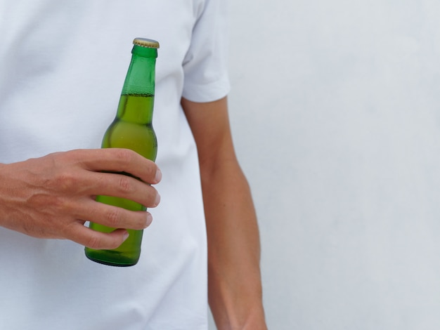 Afbeelding bijsnijden. mens in de witte fles van de t-shirtholding een bier. kopieer ruimte.