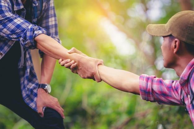 Afbeelding bijsnijden van de hand van een man die een vriend helpt om naar de top van de berg te klimmen.