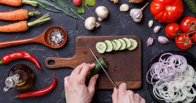 Afbeelding bovenop verse groenten, champignons, snijplank, olie, mes, handen van kok