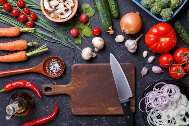 Afbeelding bovenop verse groenten, champignons, snijplank, olie, mes