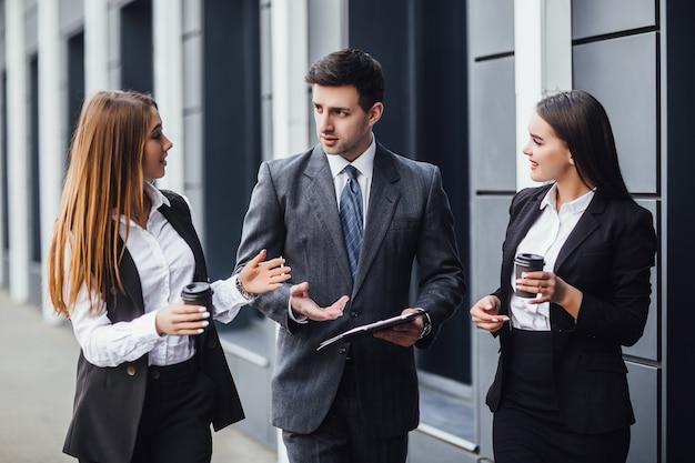 Afbeelding drie zakenpartners in een zwart, elegant pak die praten en samenwerken terwijl ze een nieuwe strategie bespreken!