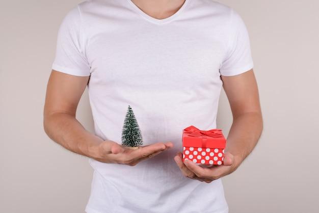 Afbeelding foto foto portret close-up weergave van gelukkig opgewonden vreugde blij man met weinig speelgoed kerstboom en doos met strik geïsoleerde grijze achtergrond