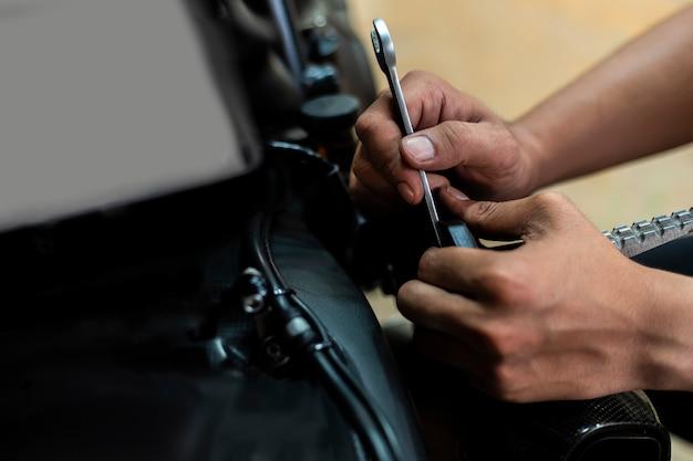 Afbeelding is close-up, auto-reparatie repareert een motorfiets gebruik een moersleutel en een schroevendraaier om te werken.