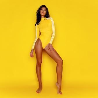 Afbeelding met een aantrekkelijke brunette vrouw die een gele bodysuit op een gele achtergrond draagt