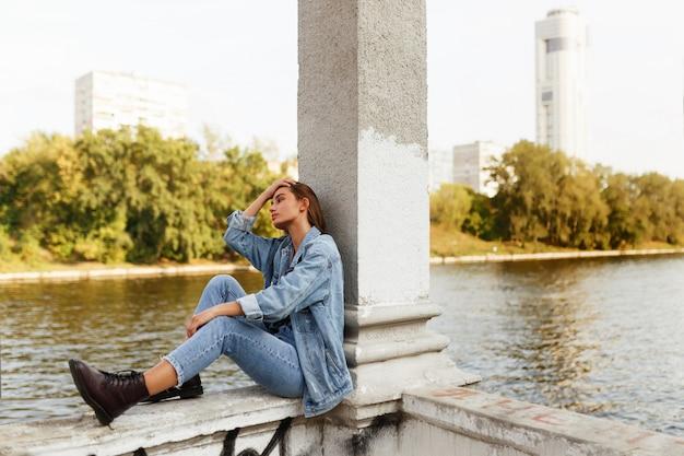 Afbeelding met een mooie brunette die naast een rivier zit