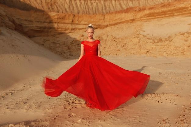 Afbeelding op volledige lengte van een prachtige jonge vrouw in een lange rode jurk die zich voordeed in de woestijn, bij de zonsondergang.