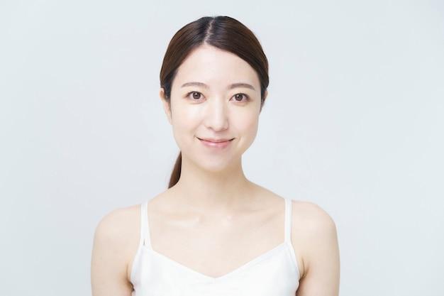 Afbeelding schoonheid / huidverzorging / glimlachende vrouw die een wit hemd draagt