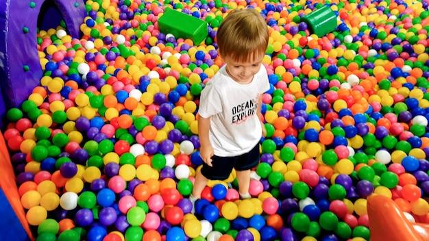 Afbeelding van 3 jaar oude peuterjongen die speelt en plezier heeft op de speelplaats met veel kleine kleurrijke plastic bal. kind genieten van pretpark in het winkelcentrum