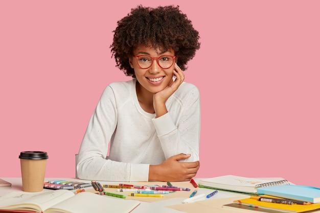 Afbeelding van aangenaam uitziende etnische vrolijke vrouw met afro-kapsel, houdt de hand op de wang, draagt een bril en witte kleren, maakt schetsen in kladblok, modellen op het bureaublad over roze muur