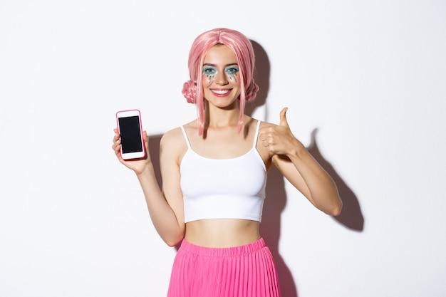 Afbeelding van aantrekkelijk jong feestmeisje in roze pruik, met lichte make-up, duimen omhoog en scherm van mobiele telefoon, app aanbevelen, staande op witte achtergrond