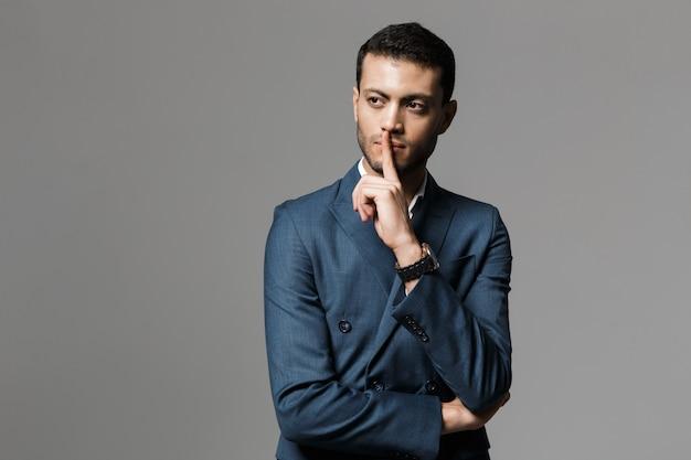 Afbeelding van aantrekkelijke arabische zakenman 30s in formeel pak met wijsvinger op de lippen, geïsoleerd over grijze muur