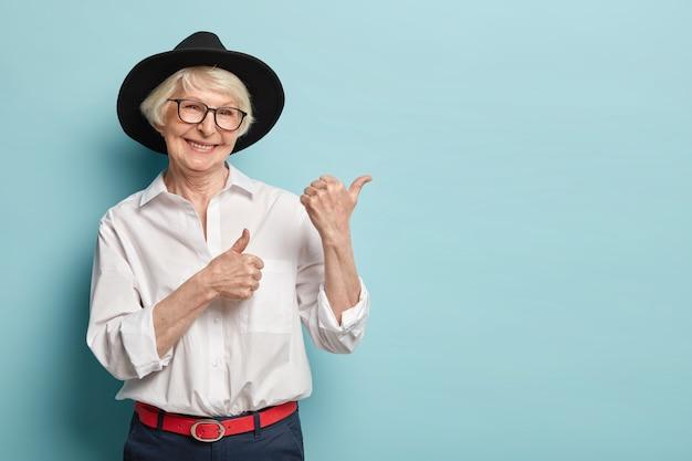 Afbeelding van aantrekkelijke gerimpelde vrouw met aantrekkelijke uitstraling, voelt zich verfrist, jong voor haar leeftijd, wijst naar de rechterbovenhoek, tevreden met het product, draagt een wit overhemd, een zwarte hoofddeksel, een optische bril