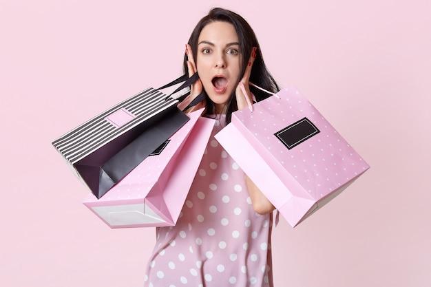 Afbeelding van aantrekkelijke geschokte vrouw, draagt boodschappentassen