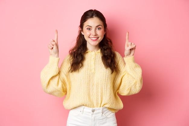 Afbeelding van aantrekkelijke jonge blanke vrouw die vingers omhoog wijst, reclame toont, glimlachend in de camera, staande tegen roze muur.