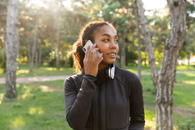 Afbeelding van aantrekkelijke vrouw 20s dragen zwarte trainingspak en koptelefoon, met behulp van mobiele telefoon tijdens het wandelen door groen park