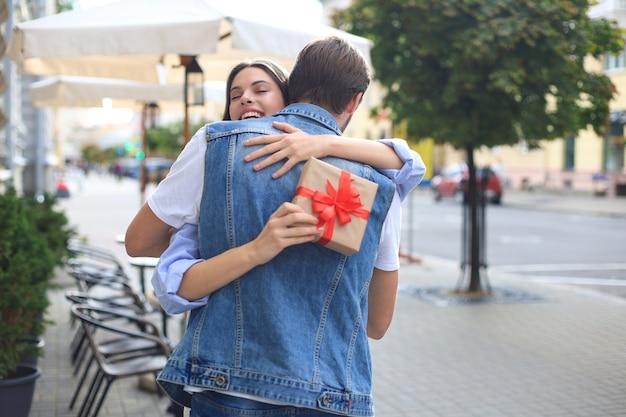Afbeelding van aantrekkelijke vrouw met huidige doos knuffel geven aan haar man.