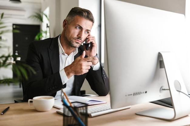 Afbeelding van aantrekkelijke zakenman 30s dragen pak praten op een mobiele telefoon tijdens het werken op de computer in kantoor