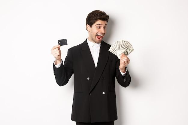 Afbeelding van aantrekkelijke zakenman in zwart pak, vreugde, creditcard tonen en kijken naar geld, staande tegen een witte achtergrond
