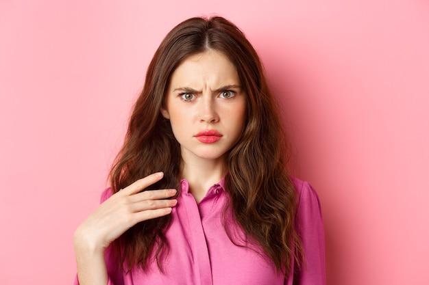Afbeelding van arrogante jonge vrouwen kijken met frustratie en minachting, beledigd worden door iets, fronsend, hand op de borst vasthouden, roze muur.