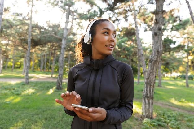 Afbeelding van atletische vrouw 20s dragen zwarte trainingspak en koptelefoon, met behulp van mobiele telefoon tijdens het wandelen door groen park