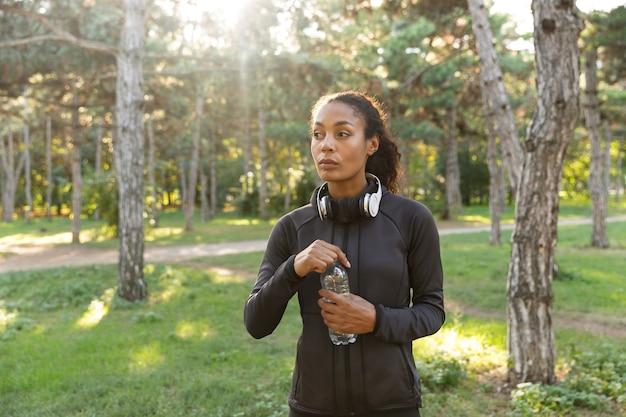 Afbeelding van atletische vrouw 20s dragen zwarte trainingspak en koptelefoon, waterfles vasthouden tijdens het wandelen door groen park