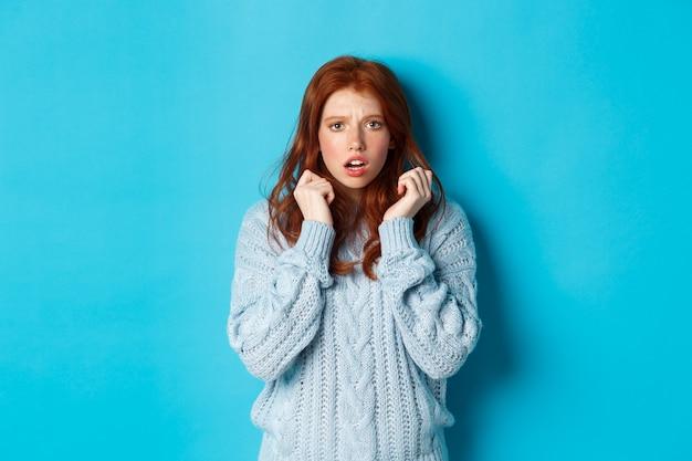 Afbeelding van bang tiener meisje met rood haar, geschrokken springen en op zoek gealarmeerd, staande over blauwe achtergrond.