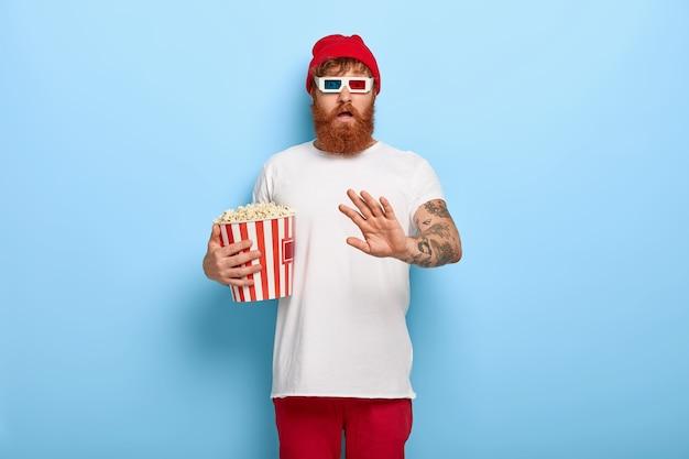 Afbeelding van bange man houdt container met popcorn