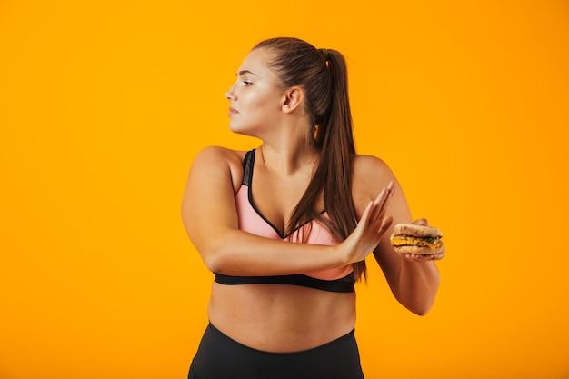 Afbeelding van blanke mollige vrouw in trainingspak doet stop gebaar terwijl sandwich, geïsoleerd op gele achtergrond