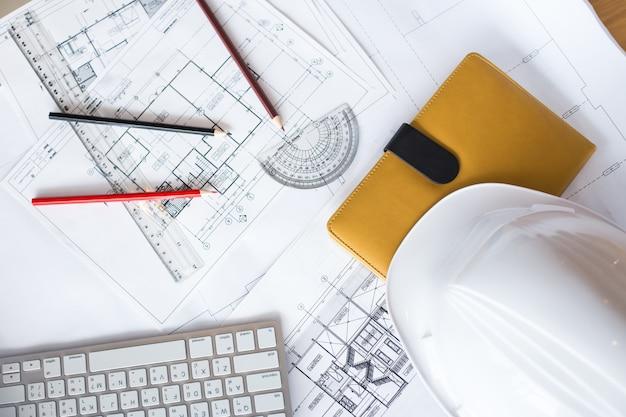 Afbeelding van blauwdrukken met level pencil en hard hat op tafel