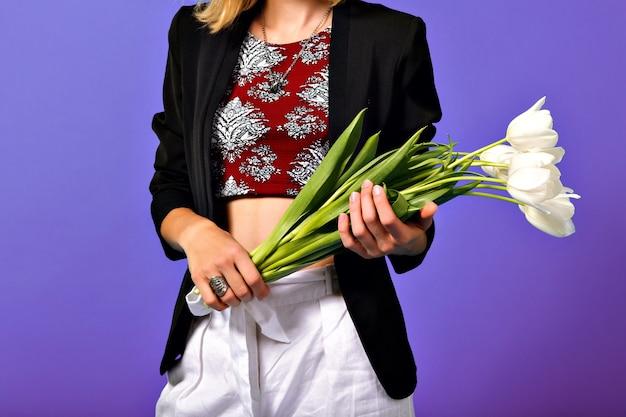 Afbeelding van boeket van witte tulpen in handen van jonge modieuze vrouw in zwarte jas geïsoleerd op paarse achtergrond.
