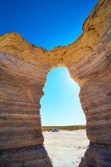 Afbeelding van boog door een pilaar van witte rots die de zon en de blauwe lucht blokkeert