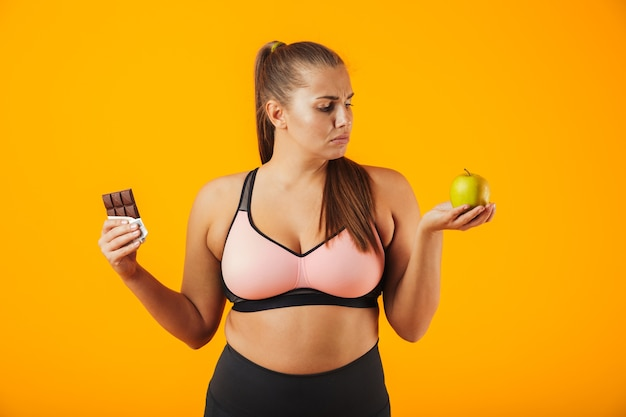 Afbeelding van boos dikke vrouw in trainingspak met chocoladereep en appel in beide handen, geïsoleerd op gele achtergrond