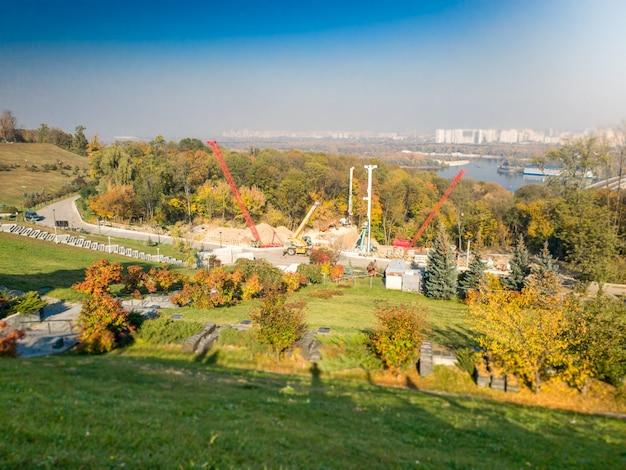 Afbeelding van bouwplaats en zware machines in prachtig herfstpark