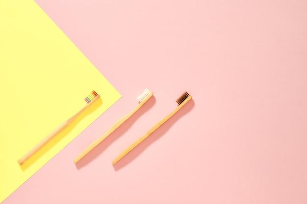 Afbeelding van bovenaf van drie houten tandenborstels met regenboogbruine en witte haren diagonaal geplaatst op een roze achtergrond met een gele driehoek in isometrisch