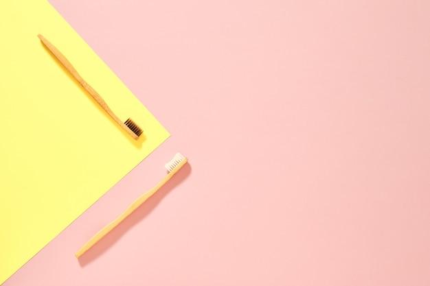 Afbeelding van bovenaf van twee houten tandenborstels met bruine en witte haren diagonaal geplaatst op een roze achtergrond met een gele driehoek in isometrisch aan de linkerkant