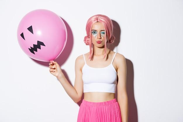 Afbeelding van brutaal mooi meisje met roze pruik en lichte make-up, ballon houden op feestje, knipogen en koket kijken, vakantie vieren.