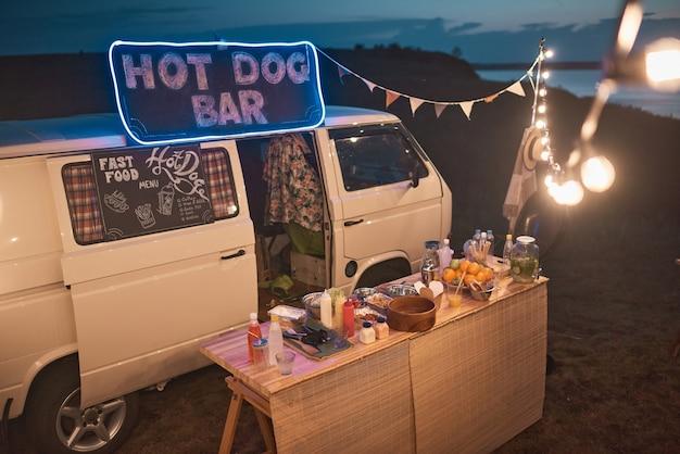Afbeelding van busje met buitenbar met eten en drinken versierd met lichtjes op strandfeest