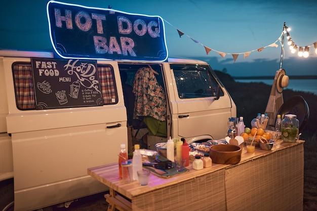 Afbeelding van busje met hotdogbar met eten en drinken op strandfeest