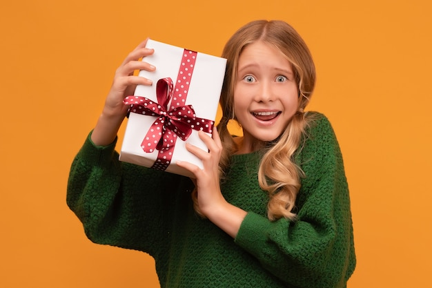 Afbeelding van charmante blonde meisje 12-14 jaar oud in warme groene trui glimlachend en huidige doos te houden